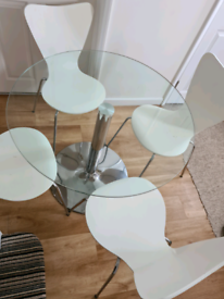 Next Glass Table with silver base and 4 white chairs