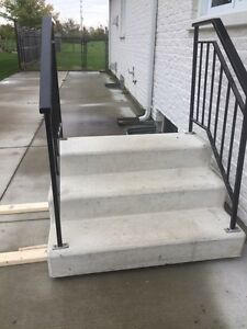 Cement steps, with black iron railing