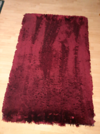 Machine tufted polyester red shaggy rug.