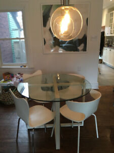 West Elm round glass kitchen table and four white chairs
