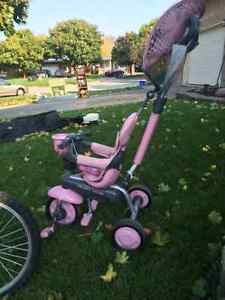 Girls push along tricycle