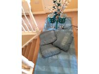 Teal curtains, cushions, lamps and vase