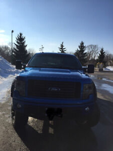 Electric blue Ford F-150 FX4 truck with 6 inch lift kit