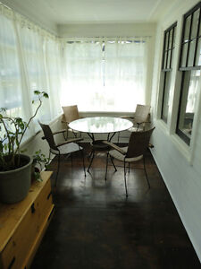 Dining set  glass top and four wicker/ cast iron chairs