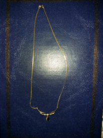 Delicate black pendant on a gold plated chain.