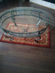 Lovely oval glass top coffee table with ornate wrought iron legs
