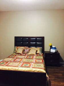 A queen size bed with dresser and a side table on sale