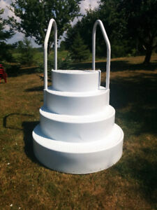 White set of four steps with rails for swimming pool.