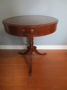 Table ronde antique en bois avec un faux tiroir.