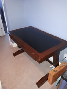 Solid wood desk with glass top and chair.