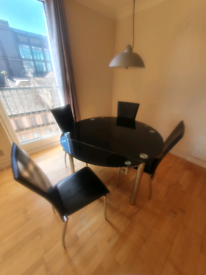 Black glass round dining table with 4 chairs