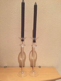 Two long, glass candleholders