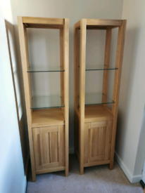 Two wooden display units with glass shelves and cupboards under.