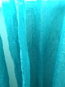Two teal curtain panels and glittery diamond rod