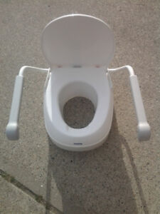 Toilet seat riser with movable arm rests
