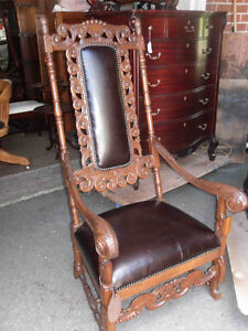 Antique tall backed ornately carved oak arm chair