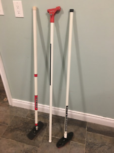 2 curling brooms and a curling stick