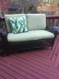 beautiful, comfortable wicker loveseat with cushions and barcart