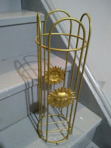 Gold painted toilet paper holder with suns