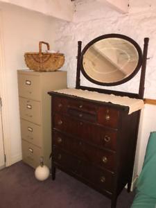 Antique tall dark wooden dresser with large oval mirror