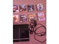 PS3 with power cords and a bundle of games and a controller