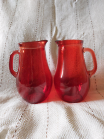Large red glass jugs.