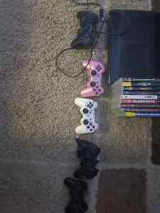Ps3 console with controllers games and steering wheel.