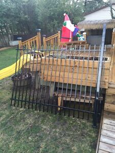 Solid new section of black metal fence and post