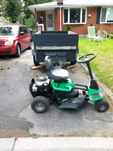 Riding lawn tractor with trailer and hedge trimmer.