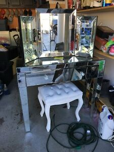 Mirror covered vanity and white leather stool with crystals