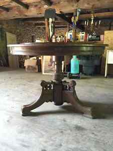 Round dark wood table with ornate base.