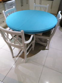 Round extending blue dining table with 4 chairs