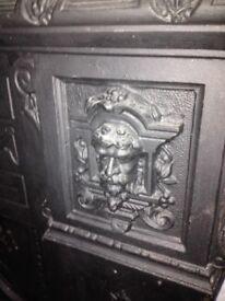 Antique figurative cast iron fireplace .