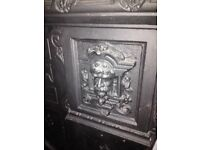 Antique figurative cast iron fireplace .