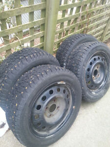 FOUR STUDDED WINTER TIRES ON RIMS