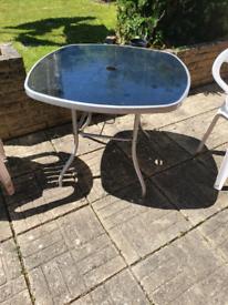 sleek glass-topped steel garden table