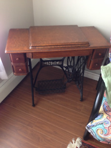 Singer Sewing Machine with a wood cabinet and wrought iron base
