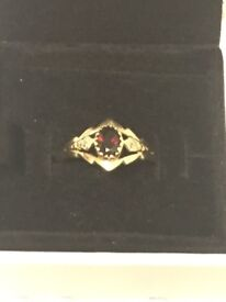 9K gold ladies ring with a red gem stone size 'S'