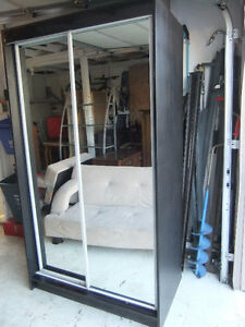 large stand alone coat closet with mirrored sliding doors