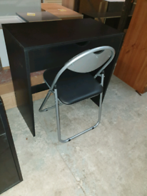 A new stylish black finish small desk with folding chair .