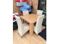 Oak table and four cream leather chairs