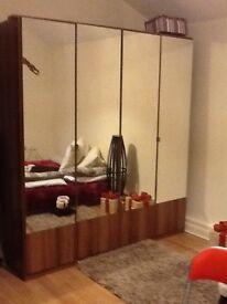 4 door mirrored wardrobe in walnut effect wood.