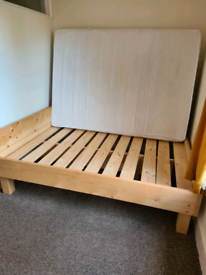 wooden double bed with a mattress