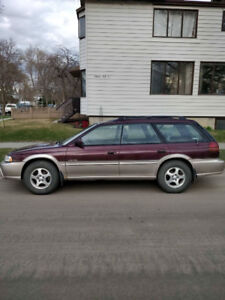 1999 Subaru Legacy Outback with Extra Rims & Roof Rack.