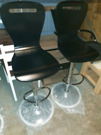 A new stylish pair of black wood and chrome breakfast bar stools .