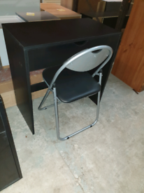 A new stylish black finish 1 drawer desk with a folding chair .