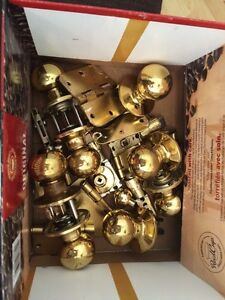 Box of secondhand brass doorknobs and hinges