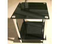 Tinted Black Glass Top and Shelf with Chrome Legs in very good condition.