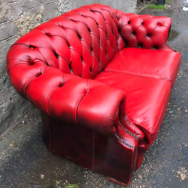 Two seater red leather chesterfield on castors