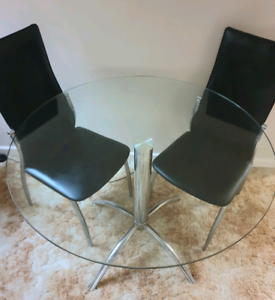 Round glass dining table, X 2 black chairs